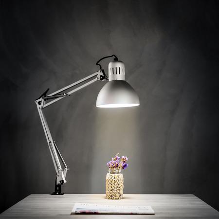 暗い部屋のコンクリートの壁の前に光のランプと木製のデスク 写真素材