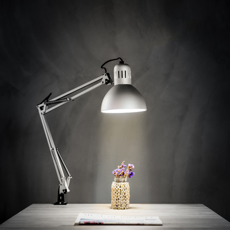 Wooden Desk with Lamp light in front of concrete wall in dark room