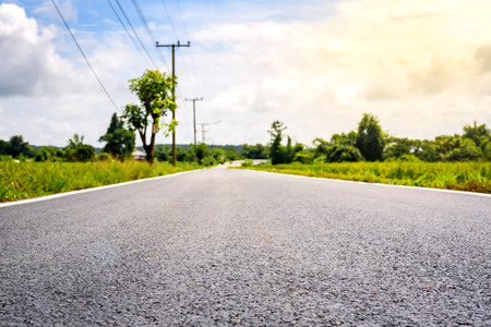 cut through: mpty country road through the agricultural fields in the morning