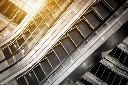 複数のステップと朝の日差しと現代のショッピング モールでエスカレーターの方向