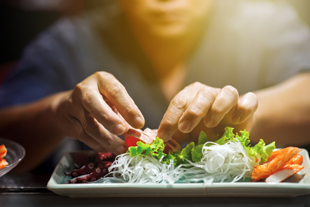 Hand of Chef Making sushi on sushi bar , dramatic lighting 스톡 콘텐츠