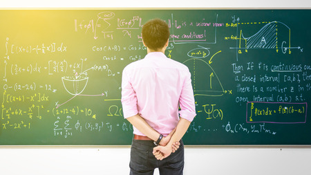 Businessman tries to solve math equation on black board Stock Photo