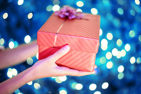 Close up of female hands holding a red gift box with blue christmas bokeh light background Stock Photo