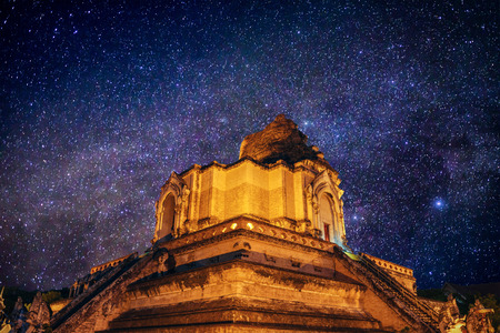 ancient pagoda Wat Chedi Luang Temple in the night with milky way in stars field , Chiang mai , Thailand