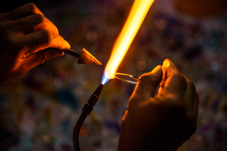 Artist works on glass , Closeup of a flame and melting glass piece