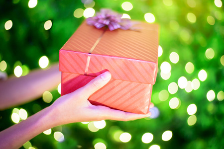 Close up of female hands holding a red gift box with green christmas bokeh light background
