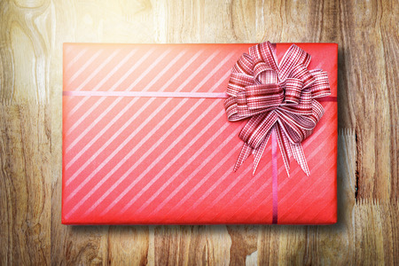 Red Gift box with bow on wooden background