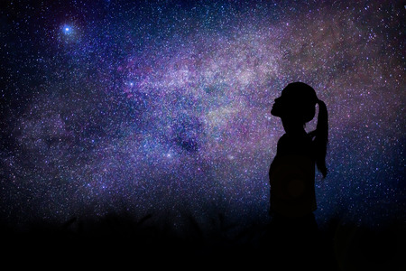 Silhouette of woman stand alone in the night with detail from the milky way and stars field background