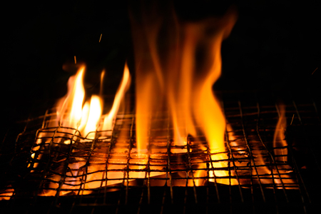 Top View Of Empty Hot Charcoal Barbecue Grill With Bright Flame On The Black Background