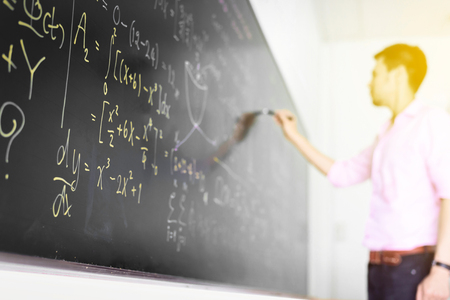 Businessman tries to problems math equation on black board ,