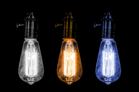 3 old style Incandescent bulbs , white warm and blue light bulb on black background Stock Photo