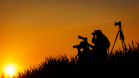 Silhouette of photographers group on grass hill in sunset evening Stock Photo - 89809972