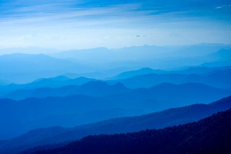 夕暮れ時の青い色の山々の層、観光と登山の概念
