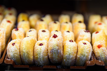 Close up view of donuts with berry jam pattern on dark background