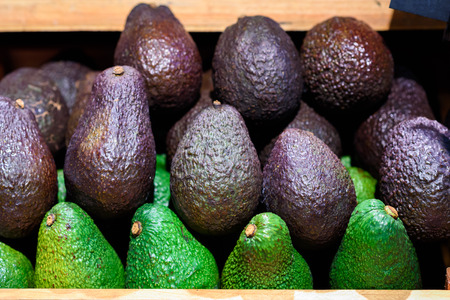 Fresh green and black avocado on a supermarket stall.