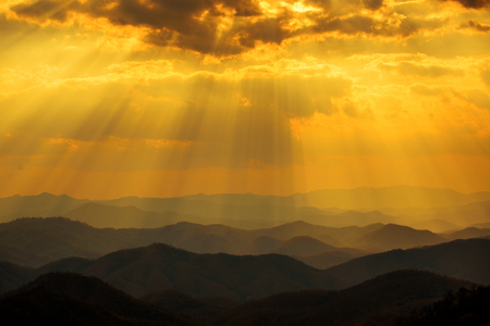 Sunset sky with sun rays over the mountains