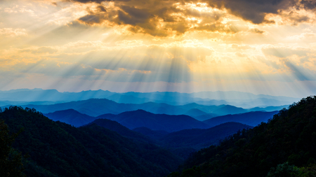 Blue mountains layers during sunset sky with sun rays Stock Photo