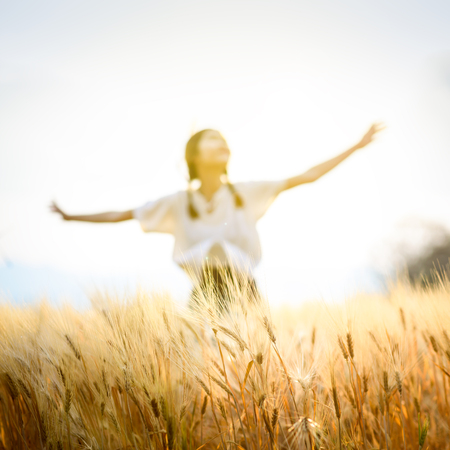 Happy woman relaxing on wheat field in summer sunset sky outdoor. People freedom open arms