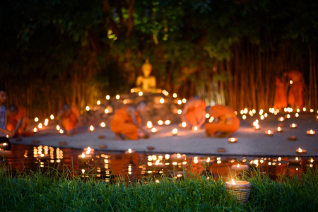 vintage style candle cup in Thai temple at night with monk background