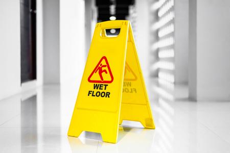 Cartel que muestra la advertencia de piso mojado en piso mojado al amanecer.