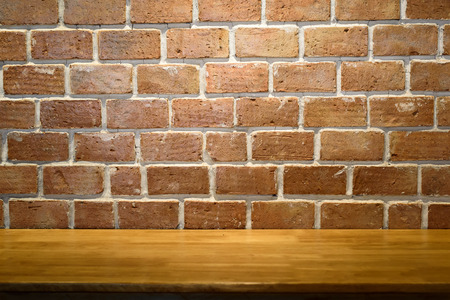 Empty top old wooden table and red brick walls backgrounds for text and background or put product