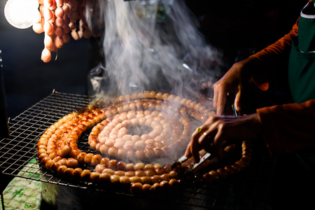 Sai Aua (Notrhern Thai Spicy Sausage ) grilling on stove at night market Stock Photo