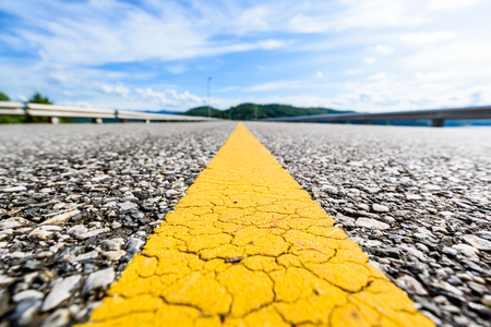 Close up of asphalt road with yellow line center