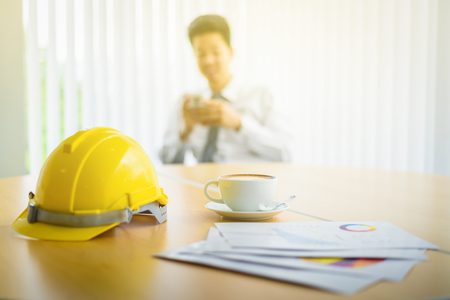 happy Architect looking Smartphone in Workplace Desktop table with Document Papers , Coffee Cup and Safety Engineer Helmet 版權商用圖片