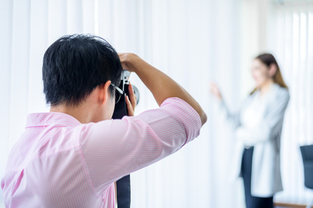 Professional Photographer Working with Model in White Office Studio