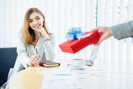Happy  smart Business woman looking red gift box in boss hand in modern office room Standard-Bild - 123201468