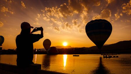 young woman using a smart phone silhouette at sunset in balloon festival