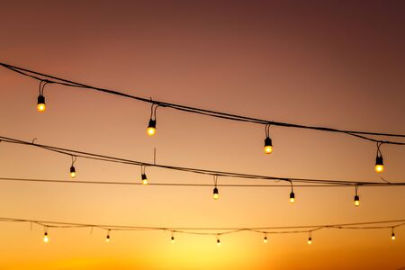 vintage light bulbs on string wire against sunset decor in outdoors wedding event party Stock fotó