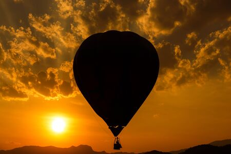 Silhouette hot air balloon over mountains in sunset sky