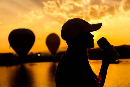 young woman drinking something form can silhouette in sunset sky in balloon festival