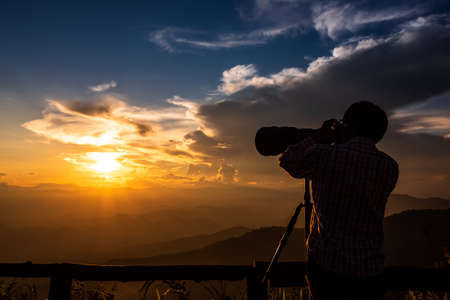 Silhouette of a landscape photographer use super telephoto lens at top of mountains during sunset sky