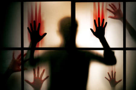 silhouette scared man with red bloody hands stand behind glass door , horror background - Image