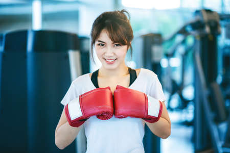 Happy attractive asian woman boxer wearing Red boxing gloves in sport fitness gym