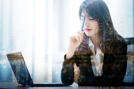 Stressed business working beautiful asian woman thinking with laptop in modern office room , double exposure with city background