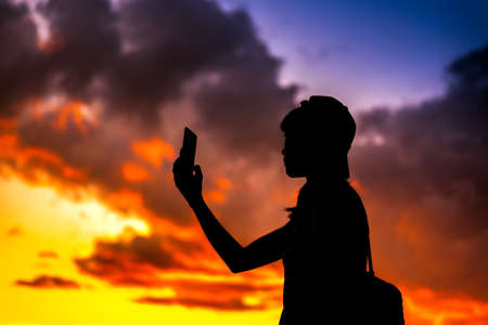 silhouette of a tourist woman holding a smartphone taking pictures with dramtic sunset sky background