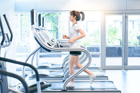 Asian girl running exercising on treadmill at sport gym , woman fitness workout.