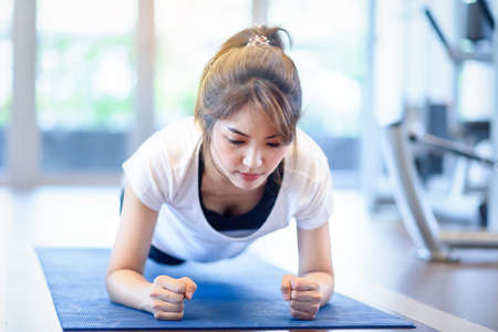 portrait  Asian woman doing plank exercising in the sports gym