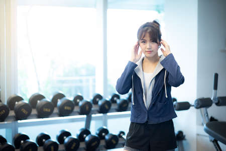 beautiful asian woman smiling with smartphone listening to music in sports fitness gym , excersie and healthcare concept Stock fotó