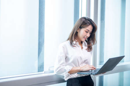Happy attractive asian business woman  smiling working with laptop in modern office Stock fotó