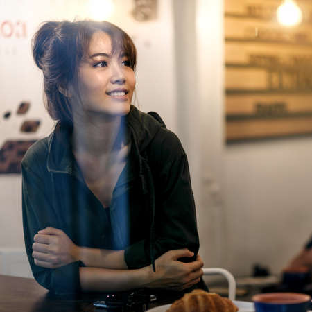 happy asian woman drinking coffee in coffee cafe