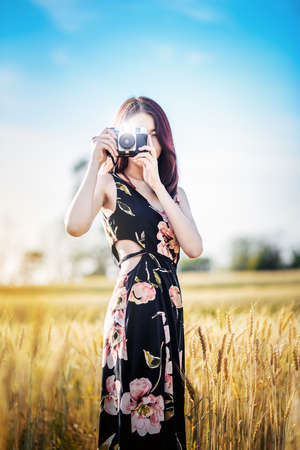 Charming asian woman Photographer holding camera on wheat summer fields in warm sunset