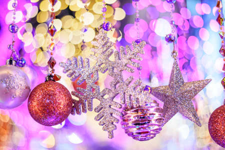 Colorful Baubles and Balls hanging decorated on christmas tree with bokeh light background