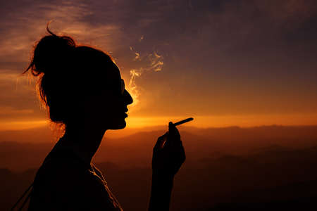 silhouette of smoking woman in sunset landscape Stock Photo