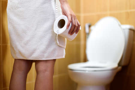 woman in towel holding toilet tissue paper roll in restroom Stock Photo