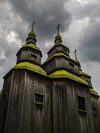 Old wooden Orthodox church on a background of storm clouds
