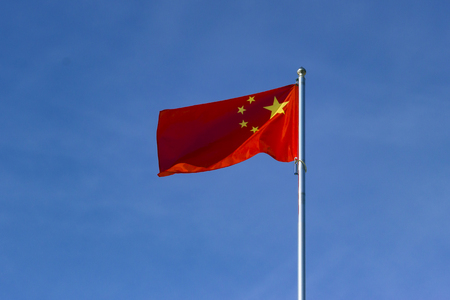 Chinese flag waving in the wind against the cloudless sky background